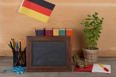 Blank blackboard, flag of the Germany, books, chancellery on table and wooden background. Learning languages concept - blank blackboard, flag of the Germany stock photos