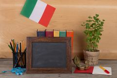 Blank blackboard, flag of the Italy, books, chancellery on table and wooden background. Learning languages concept - blank blackboard, flag of the Italy, books royalty free stock photos