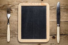 Blank blackboard, fork and knife on old table Royalty Free Stock Photos