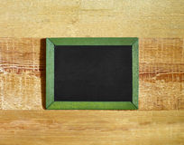 Blank blackboard in frame on wooden background Stock Photo