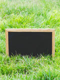 Blank blackboard on green grass. Royalty Free Stock Photo