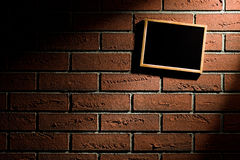 Blank blackboard hanging on brick wall Royalty Free Stock Photo