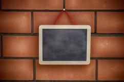 Blank blackboard hanging on a brickwall Royalty Free Stock Photography