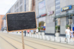 Blank blackboard label and a blurred urban landmark Stock Images