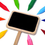 Blank blackboard label and crayons. Closeup of a blank blackboard label and crayons of different colors on a white background stock photo
