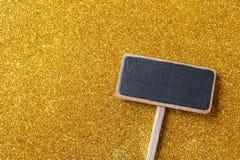 Blank blackboard label and golden glittering background Stock Photos