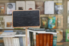 Blank blackboard label and a stack of books in the background Royalty Free Stock Images