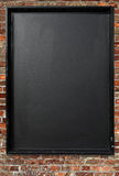 Blank blackboard menu sign on a red brick wall. Blank blackboard menu sign outside on a red brick wall Royalty Free Stock Photography