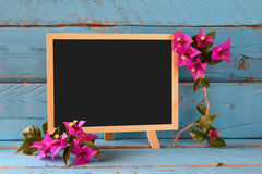 Blank blackboard next to beautiful purple mediterranean summer flowers. vintage filtered. copy space Royalty Free Stock Photo