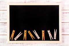 Blank blackboard and Orange clothes peg on wooden table.Template mock up for adding your design and leave space beside frame for. Adding more text stock image