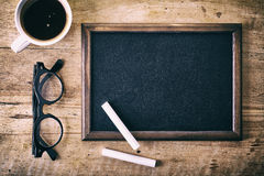 Blank blackboard. With a piece of chalk, glasses and coffee on wooden background Stock Images
