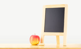 Blank blackboard with red apple on wood table at grey background Royalty Free Stock Image