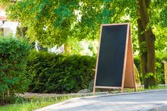 A blank blackboard sign standing on the streetside, with plants and trees around. royalty free stock photos