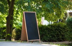 A blank blackboard sign standing on the streetside, with plants and trees around. stock photography