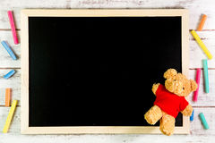 Blank blackboard and Teddy Bear on wooden table.Template mock up Stock Photo