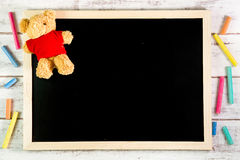 Blank blackboard and Teddy Bear on wooden table.Template mock up Royalty Free Stock Photography