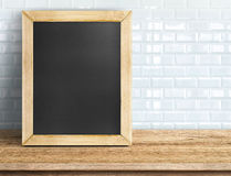 Blank blackboard on tropical wooden table at white tile wall,Tem Royalty Free Stock Photos