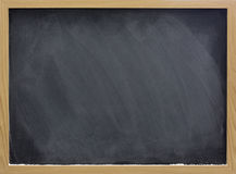 Blank blackboard with white chalk dust and smudges. Blank blackboard in wooden frame with white chalk dust and eraser smudges Stock Photo