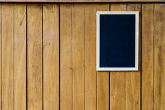 Blank blackboard on wood wall. Blank blackboard on the wood wall Royalty Free Stock Photos