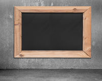 Blank blackboard with wooden frame hanging on concrete wall Royalty Free Stock Images