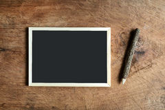 Blank blackboard and wooden pencil on old wooden Stock Photos