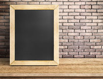 Blank blackboard on wooden table at red brick wall,Template mock Stock Images