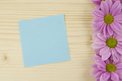 Blank blue card and pink flowers on wooden background Royalty Free Stock Photos