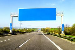 Blank blue freeway sign over the road on sunny day Royalty Free Stock Images