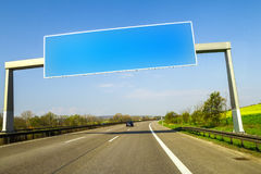 Blank blue freeway sign over the road on sunny day Stock Photos