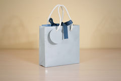 Blank blue paper gift bag mock up standing on a wooden table. Em Royalty Free Stock Image