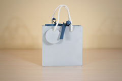 Blank blue paper gift bag mock up standing on a wooden table. Em Stock Image