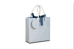 Blank blue paper gift bag mock up standing on a wooden table. Em Royalty Free Stock Images