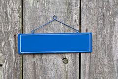 Blank blue sign on old rustic wooden fence Royalty Free Stock Image