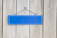 Blank blue sign on old rustic wooden fence Royalty Free Stock Images