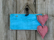 Blank blue sign with red fabric hearts and iron keys hanging on shabby wooden background Royalty Free Stock Image