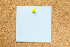Blank Blue Sticky Note. Pinned on a cork bulletin board stock images