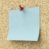 Blank blue sticky note pinned on a cork board Stock Images