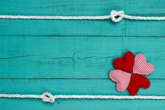 Blank blue wooden sign with collage of red hearts and rope with knots border stock photo