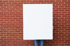 Blank board against brick wall ready for text. Blank board held by person against brick wall ready for text Stock Photos