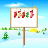 Blank board on sunny winter morning with socks Stock Photos