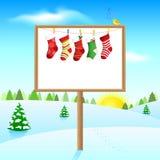 Blank board on sunny winter morning with socks Stock Photos