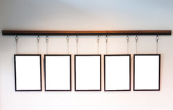 Blank boards hanging on white wall background Royalty Free Stock Photography
