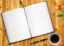 Blank book. Blank opened book outdoors on wooden disk Pen, flower and cup of tea Royalty Free Stock Photography
