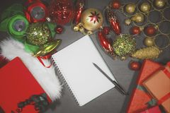 Blank book with Christmas ornaments. High angle view of a pen and empty book with Christmas ornaments on the wooden table Stock Photo