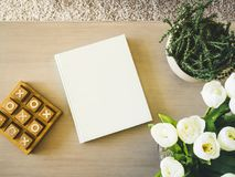 Blank Book cover on table with floral plant Home decoration. Holiday background Stock Images