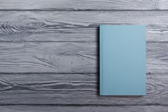Blank book cover on textured wood background. Copy Stock Photography