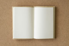 Open book with blank pages. On a brown textured surface Royalty Free Stock Photo