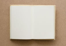 Open book with blank pages. On a brown textured surface Stock Photo