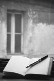 Blank book and pen. An old open blank book on a windowsill with a pen on the right side.In the background an out of focus old building with a window stock photo