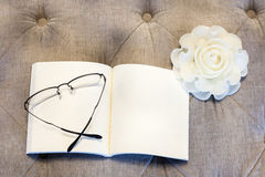 Blank book with rose candle on sofa with eyeglasses. Still life on background Stock Image